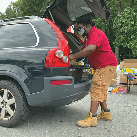 Christopher Gorden places a box of groceries into a car at a mobile food pantry in Charlotte, North Carolina, on Sept. 8. Gordon, a warehouse assistant with Loaves & Fishes, says people living with food insecurity are sometimes hesitant to ask for help despite it being available.