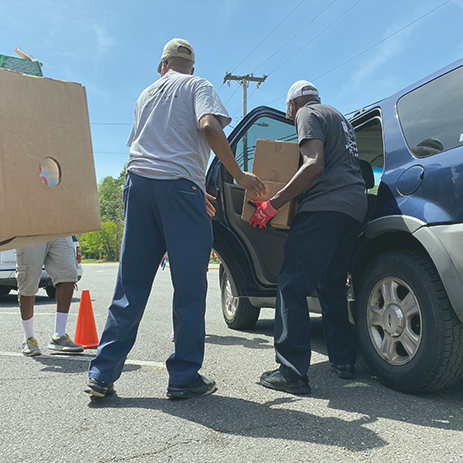 Volunteers put food in a car at a mobile food pantry in Charlotte, North Carolina, on Aug. 30.